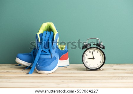 Close up of clock and sneakers - Fitness Concept