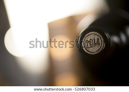Close-up of closed wine bottles lying on blurry background, winery