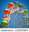 Close-up of colorful ferris wheel on vivid blue sky background - stock photo