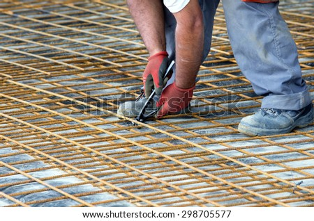 close up of construction worker hands working with pincers on fixing steel rebar at building site rebar worker
