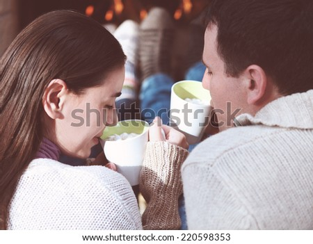 Close-up of couple holding cups with hot chocolate with marshmallows in front of lit fireplace