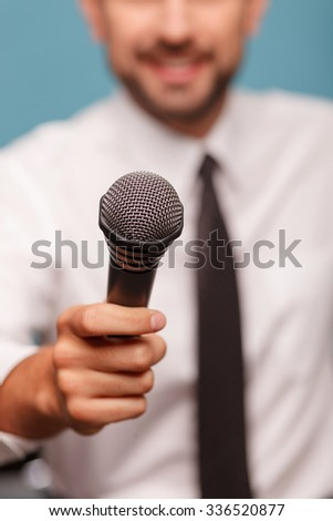Close up of cute young tv journalist is asking someone for interview. He is holding a microphone and smiling. Focus on the microphone