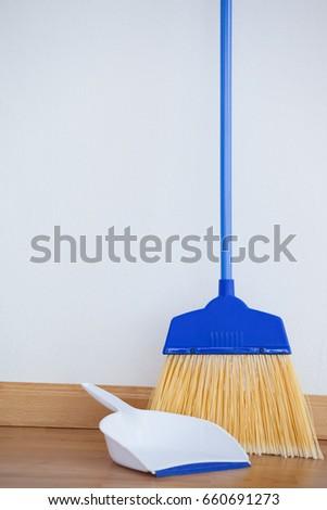 closeup of dustpan and sweeping broom on wooden floor