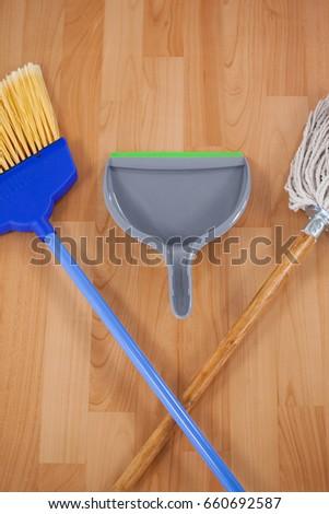 closeup of dustpan sweeping broom and mop on wooden floor