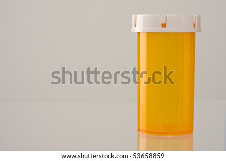 Close up of empty medicine bottle with reflection.  Lots of copy space. Concept of healthcare and medical topics.