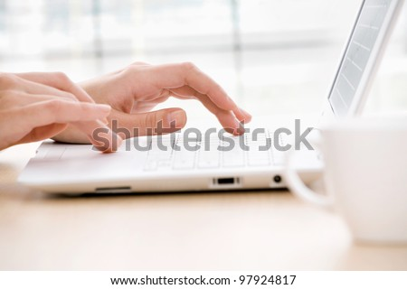 Close-up of female fingers typing a business document on the laptop