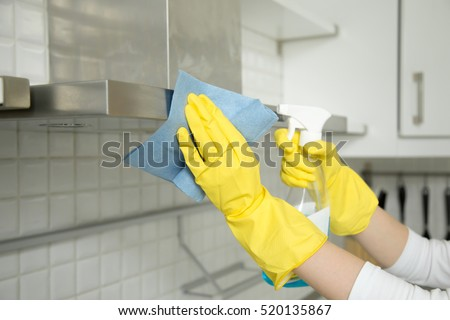 Close up of female hands in rubber protective yellow gloves cleaning the kitchen metal extractor hood with rag and spray bottle detergent. Home, housekeeping concept
