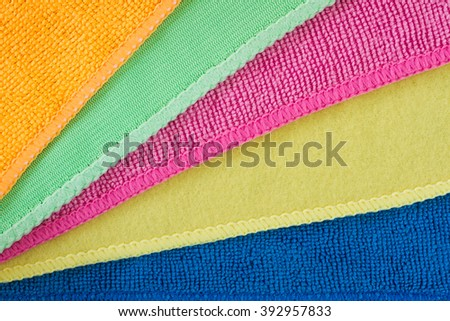 Close-up of five overlapping microfiber cleaning clothes of different colors