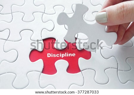 Close up of girl's hand placing the last jigsaw puzzle piece with word Discipline