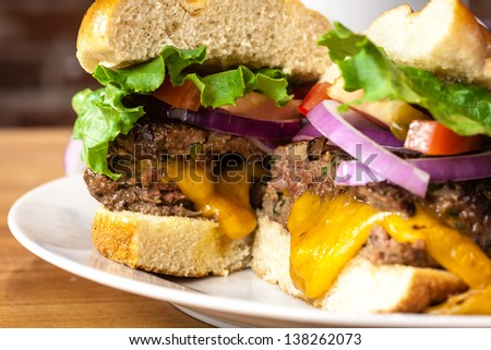 Close up of gourmet cheeseburger with melted cheese, tomatoes, lettuce and onions sitting on white plate
