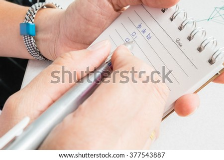 Close-up of  hand holding person's hand writing things To Do List on paper / notepad