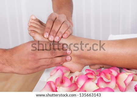 Close-up Of Hand Massaging Foot In Spa