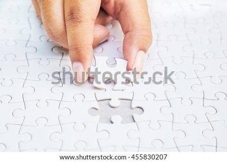 Close up of hand placing the last jigsaw puzzle piece, Hand holding missing jigsaw puzzle piece down in to the place, conceptual of problem solving, finding a solution.