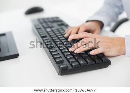 Close-up of hands typing on a keyboard in an office