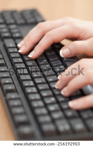 Close-up of hands typing on a keyboard in an office.