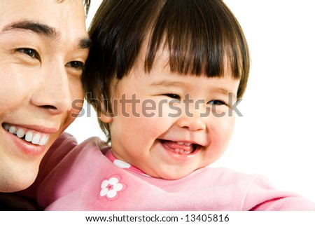 Close-up of happy father with daughter looking aside and laughing