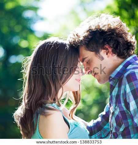 Close-up of happy man embracing his girlfriend outdoors with eyes closed.