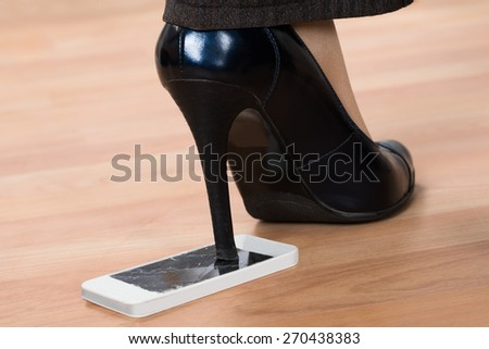 Close-up Of High Heel Step On Broken Screen Smartphone