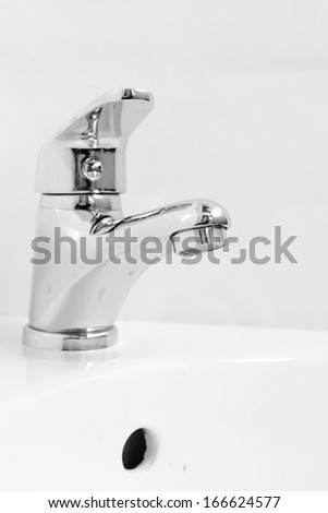 Close-up of human hands being washed under faucet in bathroom, on light background