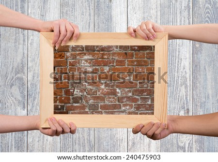 Close up of human hands holding wooden frame with brick texture