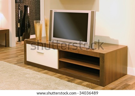 Close up of living-room with TV set and cupboard.