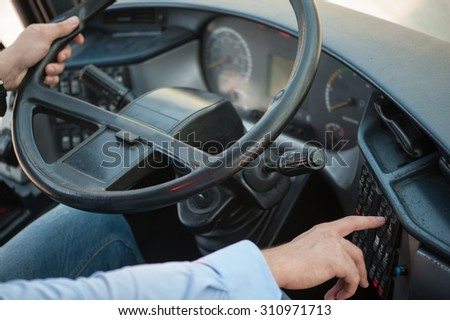 Close up of male arms holding a steering wheel. The man is sitting and driving a bus