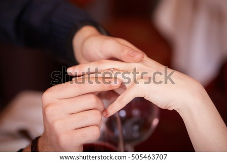 Close Up Of Male Hand Inserting An Engagement Ring Into A Finger