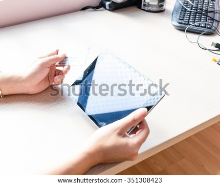 Close-up of man hands with tablet and credit card as online shopping or online payment concept. Selective and shallow focus.
