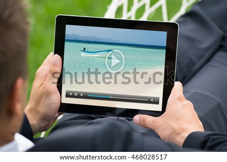Close-up Of Man In Hammock Watching Video On Digital Tablet