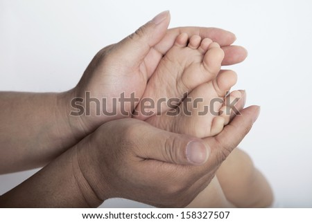 Close up of mothers hands holding the feet of her son
