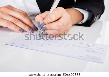 Close-up Of Person's Hand Signing Cheque On Desk