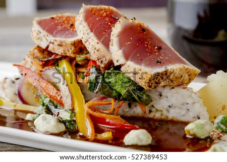 Close up of rare seared Ahi tuna slices with bok choy stir fry vegetables sitting on jasmine rice with glass of wine in background