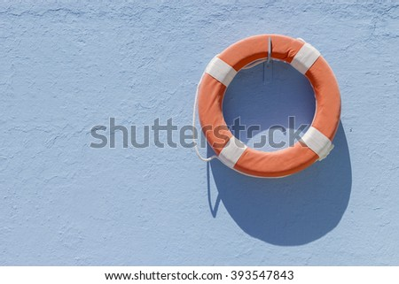 Close-up of red circular lifebuoy hanging on blue wall
