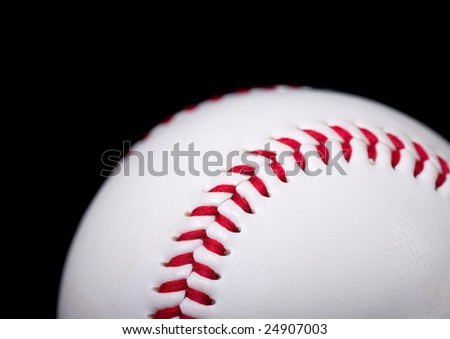 close-up of red stitches on white baseball on black background