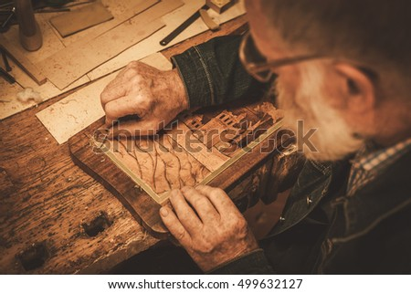 Close-up of restorer hands working with antique decor element in his workshop