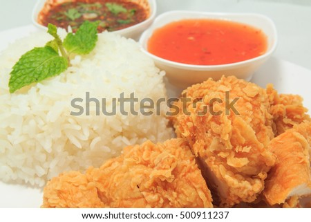 Close up of rice with fried chicken and Thai style sauce and chili sauce