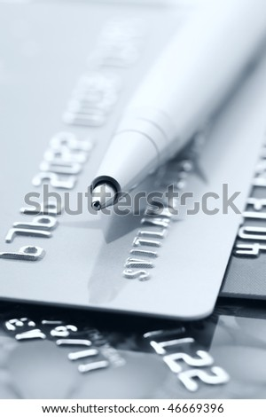 Close-up of silver pen on credit cards. Toned monochrome image. Selective focus on top of pen.