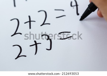 Close-up of simple math written on white piece of paper.