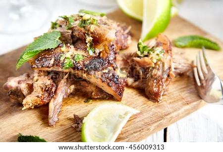 Close up of sliced cuban style slow roasted pork shoulder in mojo marinade and sauce on wood board with limes and mint near it. White wood background with brown rice bowl and pan on back