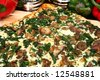 Close up of spinach and portobello mushroom pizza in kitchen or restaurant. - stock photo