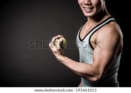 Close-up of strong man holding green apple