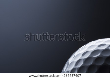 Close up of stylish golf ball isolated on dark blue background, copy space for text.