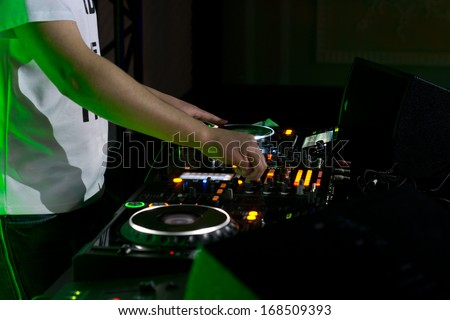 Close up of the hands of a young male disc jockey mixing and blending music tracks on his deck in the darkness of a party or nightclub
