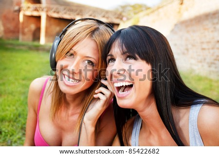 Close-up of two young beautiful girl / listening music outdoor