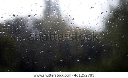 Close-up of water droplets on glass. Rain drops on window glass with blur background. Blurred tree and sky. Rainy days, rain running down window, bokeh