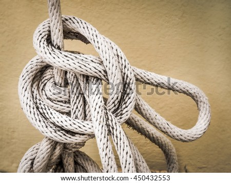 Close up of white rope And Knot on yellow cement wall