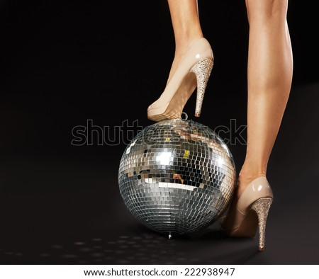 Close-up Of Woman's Foot Wearing Stilettos Over Disco Ball