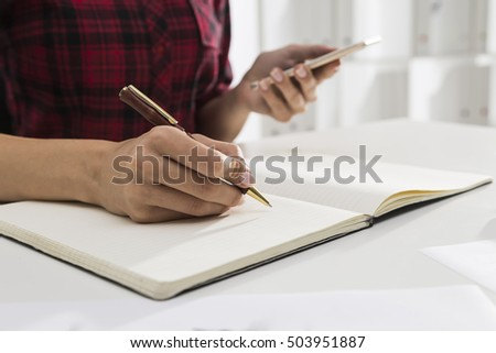 Close up of woman's hands writing in large notebook lying on the talle in white office while she is holding her smartphone. Concept of dying art of handwriting