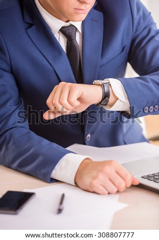 Close-up of young businessman is looking at the watch.