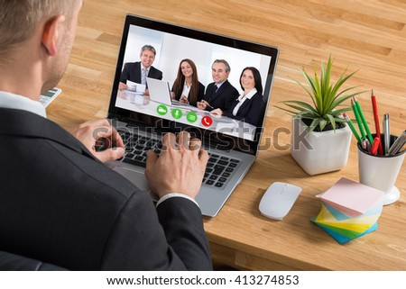 Close-up Of Young Businessman Video Conferencing On Laptop At Desk In Office